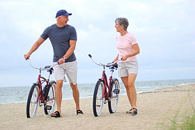 Image of a couple with bikes on a beach
